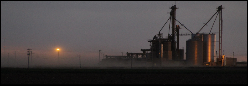 Industrial equipment is shrouded in a fog that extends out across the plains in the background and soften the sun.